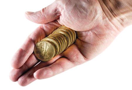 격리 된 배경으로 오래 된 남성 손에 골드 독수리 동전의 스택