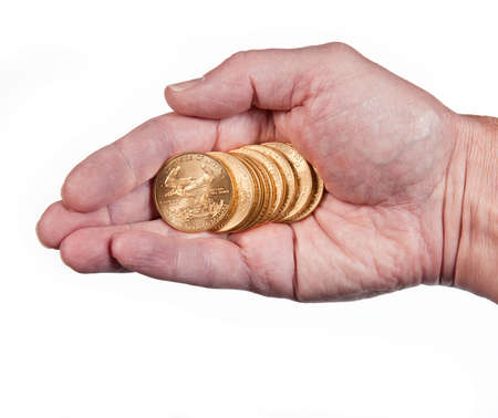 Male hand holding a stack of pure gold eagle coins