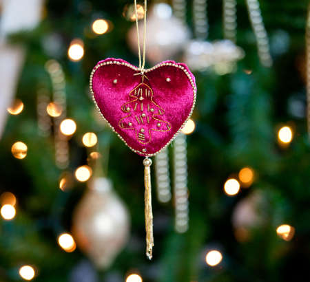 Close up of red velvet heart ornament in front of out of focus christmas decorations photo