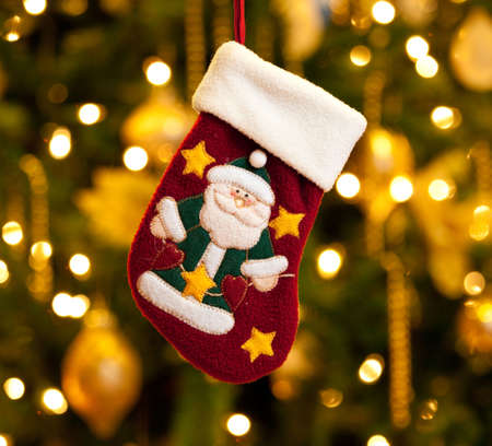 Close up of child's christmas stocking in front of out of focus Christmas tree Stock Photo - 6002466