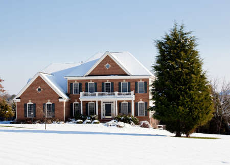 winter window: Modern home in a snowy setting with a conifer in the foreground