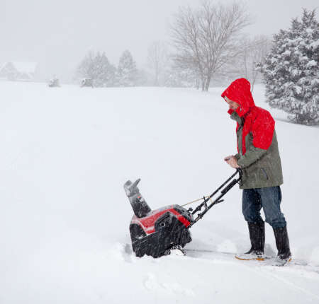Senior man in red coat using a snow blower during a blizzard on home drive photo