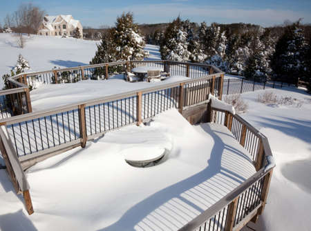 Two tier deck covered with deep snow covering a small wooden table and chairs photo