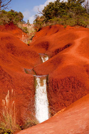 Water running in a stream down the bright red dirt of Waimea Canyon in Kauai photo