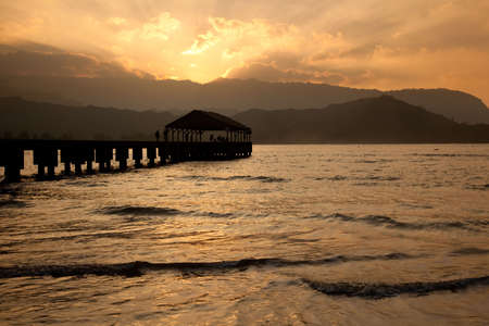 Sun setting behind Na Pali mountains with a silhouette of Hanalei Pier photo
