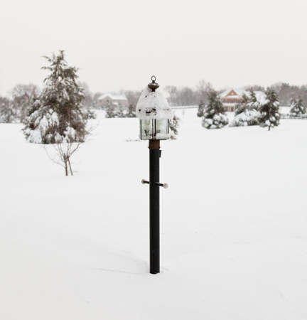 Black lamp post buried in deep snow by covered road