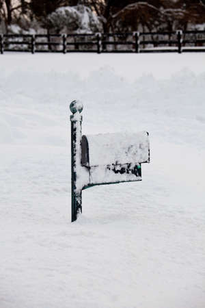 Green mailbox buried in deep snow by covered road