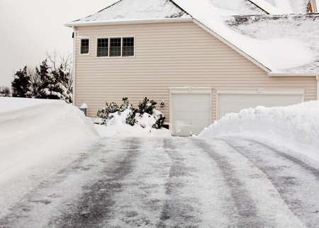 High snow banks by side ofdrive leading to a modern house photo