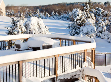 Wooden table and chairs buried deep in snow on deck after blizzard Stock Photo - 6371107