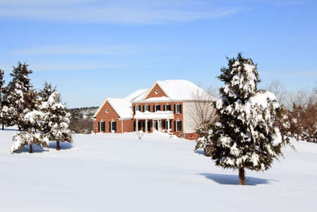 Modern home in a snowy setting with a conifer in the foreground photo