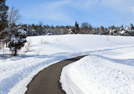 High snow banks by side of road leading up a hill after recent plowing Reklamní fotografie