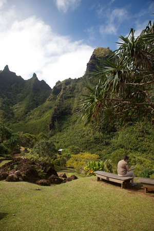 mountain ranges: Middle aged woman sitting on bench overlooking Kauai mountain ranges