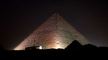 Giza Pyramids and sphinx illuminated by colored lights at night photo