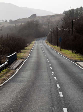 the carriageway: A single carriageway road leads into the distance among hills and meadows