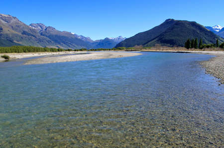 Mountain range tower over tranquil river near in Paradise area of New Zealand photo