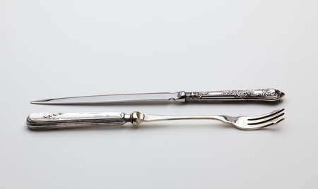 Old fashioned sterling silver objects being a decorated knive and fork used for cakes photo