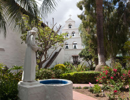 Garden of San Diego mission with bells framed by saint statue and well photo
