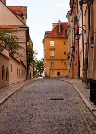 Old ornate lanterns in front of the orange facades of old buildings in Warsaw Poland photo