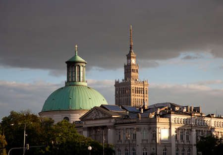 Palace of Culture and Science is framed by a domed church at sunset in Warsaw Poland photo