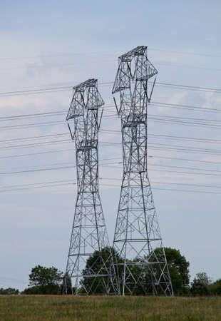 Las torres de electricidad de metal grande de marzo a trav�s de la campi�a  Foto de archivo - 7260454