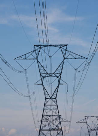 Large metal electricity pylons march across the countryside photo