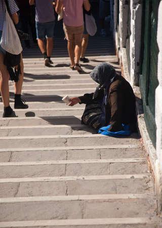 Beggar on steps in Venice on Grand Canal Reklamní fotografie
