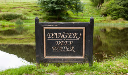 drown: Sign warning of deep water by reflecting pond