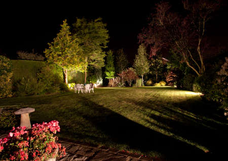 lighting: Well tended garden and flowers floodlit at night Stock Photo