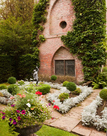 Formal flower beds in front of old brick building with statue