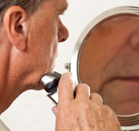 Retired male shaving with electic razor in front of magnifying mirror photo