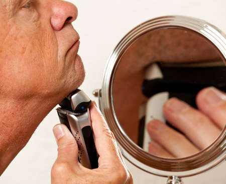 Retired male shaving with electic razor in front of magnifying mirror Stock Photo - 7850983