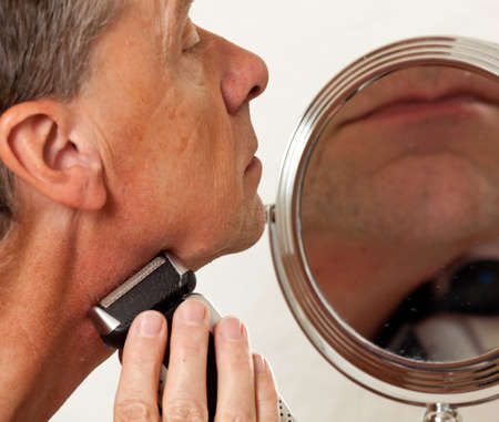 Retired male shaving with electic razor in front of magnifying mirror Stock Photo - 7850984