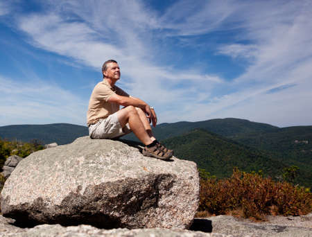 overlook: Senior hiker looks over valley in the Shenandoah on a climb of Old Rag