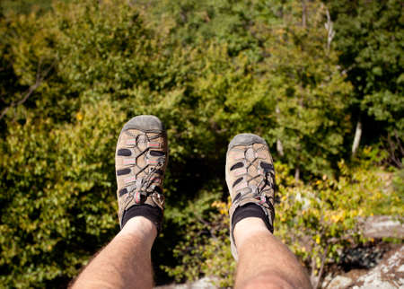 Hiker looks over valley in the Shenandoah on a climb of Old Rag with feet hanging on the edge photo