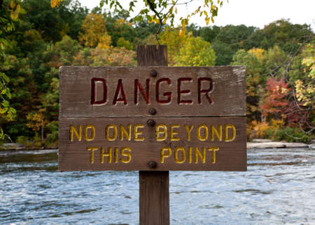 Wooden painted danger sign by rushing river photo