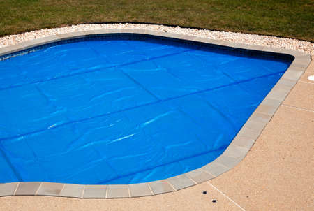 Bubble wrap like pool cover pulled over a swimming pool to keep in heat overnight photo