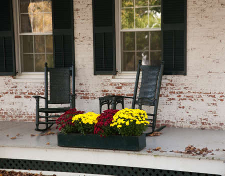 Pair of old rocking chairs on porch of old building in fall photo