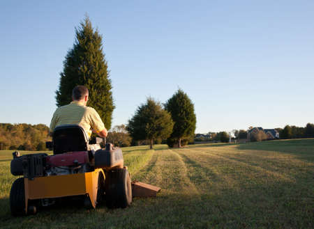 Middle aged man on zero turn mower cutting grass on a sunny day with the sun low in the sky photo