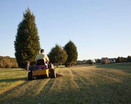 Midden oude mens op nul zetten maaier snijden gras op een zonnige dag met de zon laag aan de hemel Stockfoto