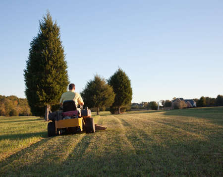 Middle aged man on zero turn mower cutting grass on a sunny day with the sun low in the sky