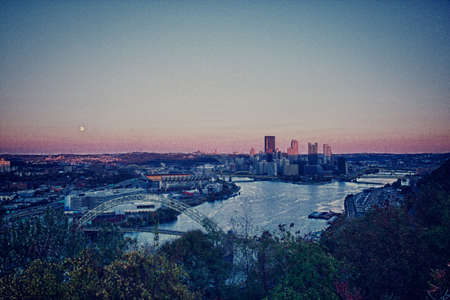 Unusual paint like view of the city of Pittsburgh at sunset as the moon rises over the horizon photo