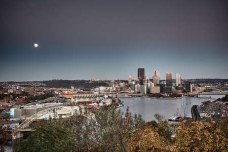 overlook: Unusual paint like view of the city of Pittsburgh at sunset as the moon rises over the horizon Stock Photo