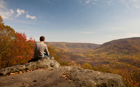 Young male hiker in jeans pondering while sitting on a boulder in front of fall leaves