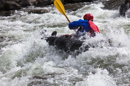 Canoeing in white water in rapids on river photo