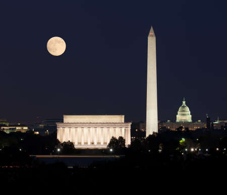 national monuments: Full Harvest moon rising above the Lincoln Memorial with Washington Monument and Capitol building aligned