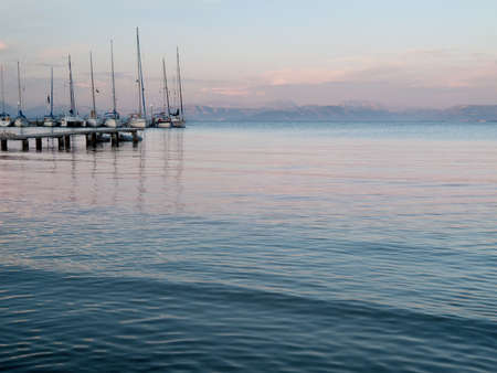 Sunset over the calm waters of the mediterranean with yachts tied up at the dock photo