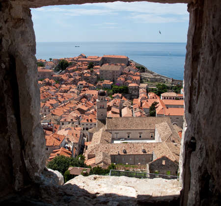 View over rooftops of Dubrovnik to tower and distant ocean photo