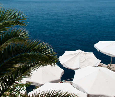 Shade provided by umbrellas on patio by ocean