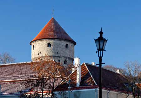 Tower on the town walls in Tallinn in Estonia in winter with snow on red tiled roofs and ornate lamp in foreground Stock Photo - 8287389