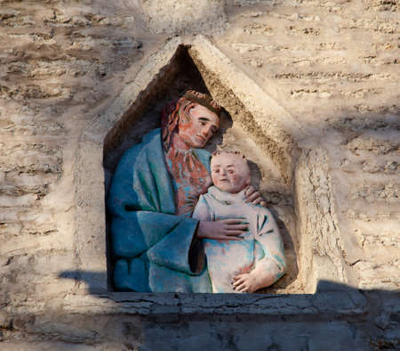 Carving of Jesus and child in an old wall in Tallinn Estonia on the climb to Toompea Stock Photo - 8287479